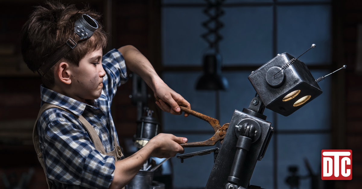 boy with dirty face using pliers to create a robot