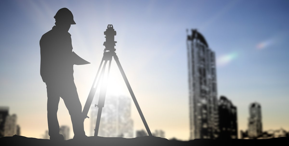 silhouette of engineer in hard hat with skyscrapers in background