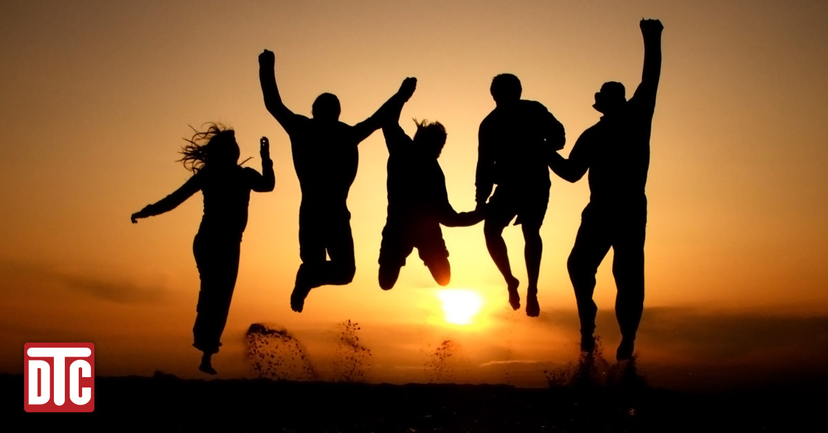 silhouettes of a group of people jumping in celebration with sunset behind